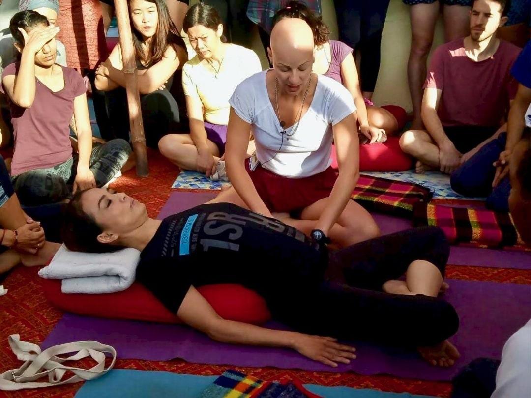 Yoga Teaching supta swastikasana at the Yoga Festival, in Rishikesh, India