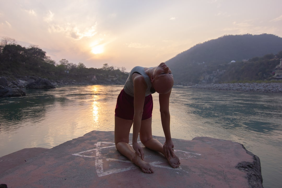 Yoga Ustrasana Final Pose back view, at sunset by the Ganges in Rishikesh, India