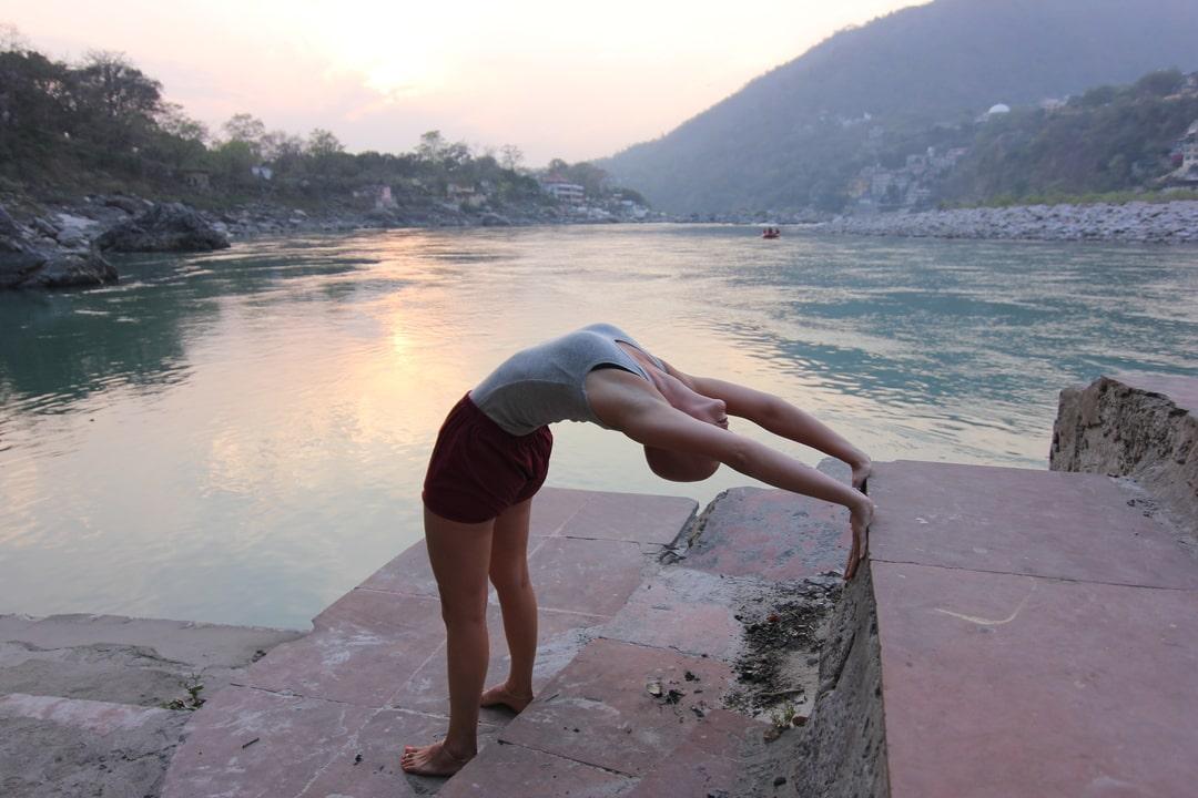 Yoga extensão atrás jutno ao Ganges, ao por do sol em Rishikesh, India