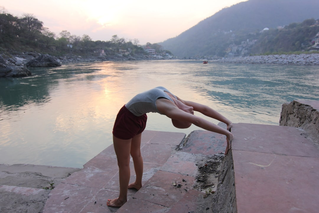 Yoga Back Bend by the Ganges, at sunset, Rishikesh, India