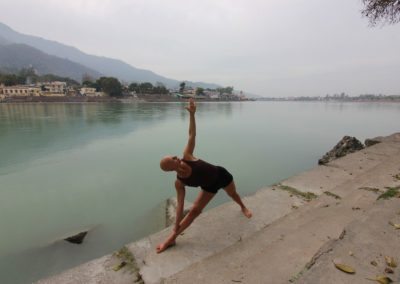 Yoga Utthita Trikonasana, extended Triangle Final Pose front view, by the Ganges in Rishikesh, India