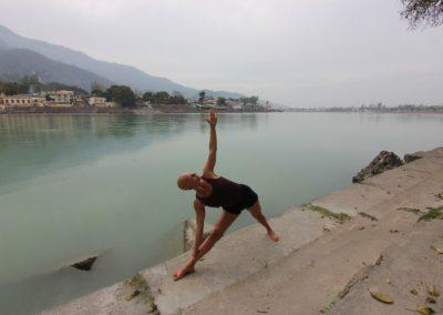 Yoga Utthita Trikonasana, postura do triangulo, junto ao Ganges em Rishikesh, India