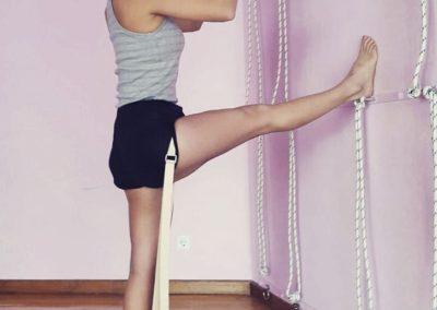 Yoga Utthita hasta padangusthasana na parede e com cordas