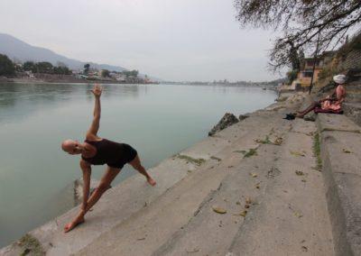 Yoga Utthita Trikonasana, extended Triangle Final Pose, by the Ganges in Rishikesh, India