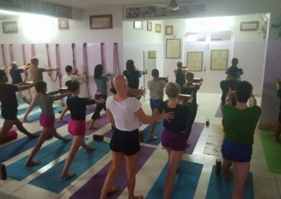 A ensinar Yoga Virabhadrasana I com props em Rishikesh, India